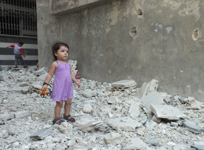 A girl stands on debris next to a damaged building at a besieged area of Homs